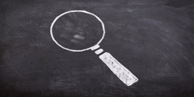 magnifying glass on chalk board